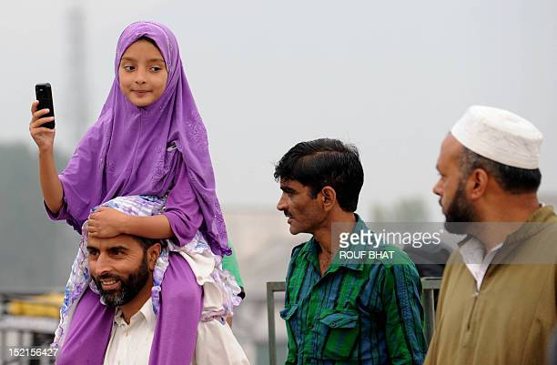 Kashmiri Muslim girl take a picture from mobile phone to Kashmiri pilgrims departing for Mecca for the annual Hajj pilgrimage in Srinagar on...