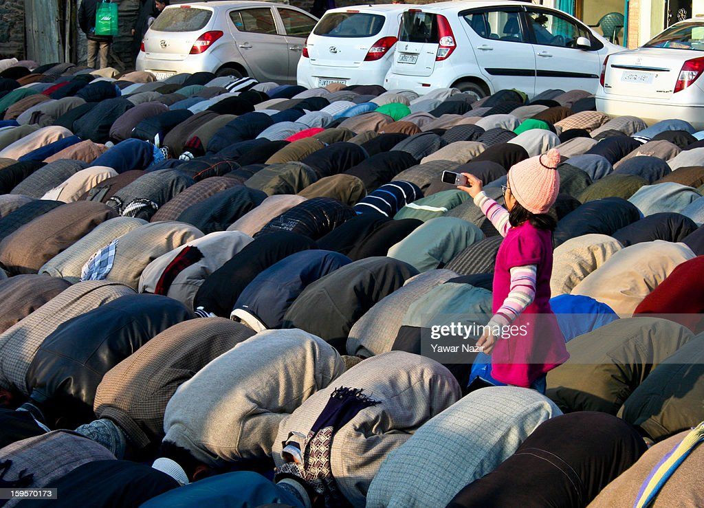 A Kashmiri Muslim girl takes pictures with her mobile phone of Kashmir Muslims offering prayers outside the shrine of Khwaja Naqshband on January 16, 2013 in Srinagar, the summer capital of Indian-administered Kashmir, India. Thousands of devotees from across Kashmir converge at the shrine of Khwaja Naqshband Sahib in downtown Srinagar to participate in annual congregational prayers called 'Khoja Digar' on the 3rd of Rabi-ul-Awal, the third month of the Islamic calendar.