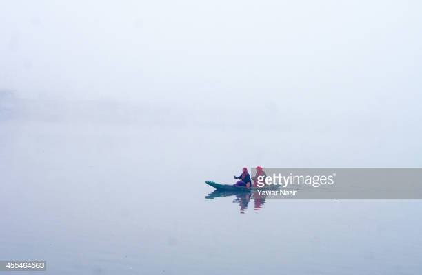 Kashmiri Muslim girls row a boat in Dal lake during a cold foggy day on December 12 2013 in Srinagar the summer capital of Indian administered...