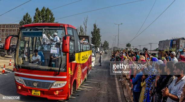 Kashmiri Muslim hajj pilgrims wave from a bus towards their relatives before departing for the annual Hajj pilgrimage on July 26 2017 in Srinagar the...
