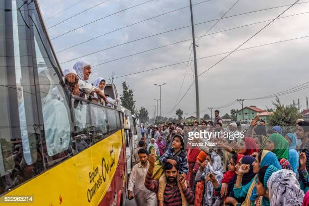 Kashmiri Muslim hajj pilgrims wave from a top a bus towards their relatives before departing for the annual Hajj pilgrimage on July 26 2017 in...
