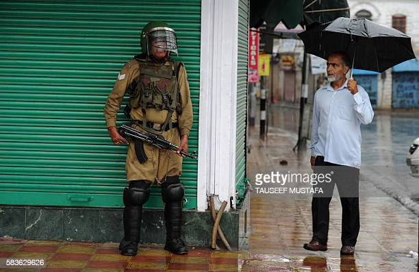 Kashmiri muslim looks at an Indian paramilitary trooper standing guard amidst a heavy rainfall during curfew in Srinagar on July 27 2016 / AFP /...
