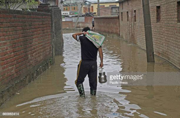 Kashmiri Muslim man carry eatable stuff to his family in flooded area in Srinagar Indian Controlled Kashmir on Friday April 7 2017 Six people...