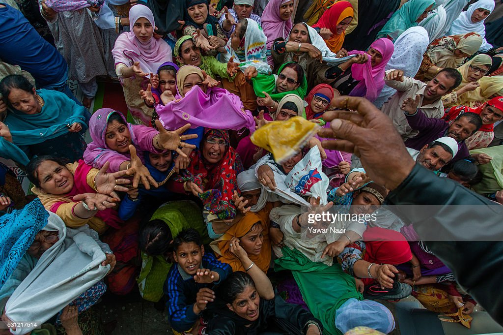 Kashmiri Muslim man distributes food among Muslim devotees at the Hazratbal Shrine on the Friday following MehrajuAlam which marks ascension day the...