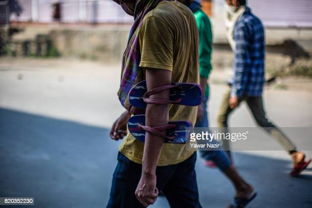 Kashmiri Muslim man inserted his arm in his slippers prepares to throw stones at Indian government forces during the funeral procession of Tanveer...