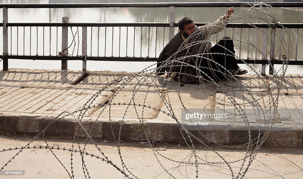Kashmiri muslim man man tries to free himself after becoming snared in concertina razor wire, during a curfew, imnposed after the execution of alleged Indian parliament attacker Mohammad Afzal Guru on February 11, 2013 in Srinagar, the summer capital of Indian Administered Kashmir, India. Afzal Guru, from Sopore town in the north of Kashmir, was hung on February 09 for his role in the 2001 Indian parliament attack which left 14 dead. The hanging has further strained relations between India - who blamed the attack on 'Pakistan backed' militant group Jaish-e-Mohammed - and neighbouring Pakistan and has seen an military increase from both along the border.