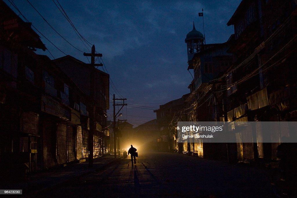 Kashmiri muslim man negotiates curfew imposed streets on February 04 2010 in Srinagar Kashmir India Soldiers dressed in riot gear patrolled the...