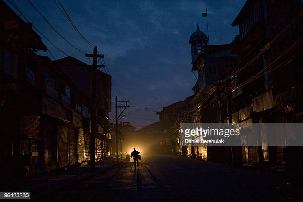 Kashmiri muslim man negotiates curfew imposed streets on February 04 2010 in Srinagar Kashmir India Soldiers dressed in riot gear patrolled the...