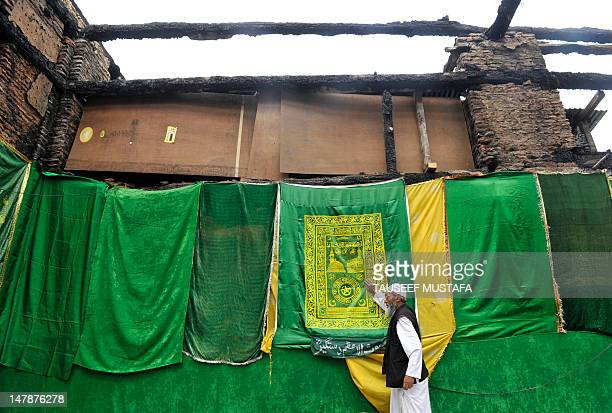 A Kashmiri Muslim man touches the ruins of a revered 200year old sufi shrine in downtown Srinagar on July 5which was gutted in a devasted fire...