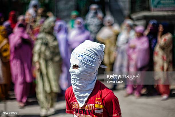 Kashmiri Muslim masked protester stands in front the women protesters shouting anti Indian and pro Kashmir Independence slogans during a protest...