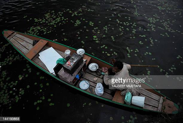 A Kashmiri muslim meat sticks seller navigates on dal lake on a windy and rainy day in Srinagar on May 11 2012 Pakistan said that it would host the...
