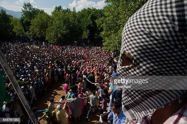 Kashmiri Muslim men and women jostle to have th glimpse of Burhan Wan a top Hizbul Mujahideen commander killed in a brief gun battle with Indian...