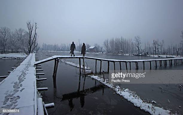 Kashmiri Muslim men walking over the wooden bridge near the floating market The Valley continue to received snowfall from past couple of days while...