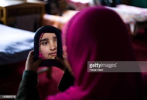 Kashmiri Muslim orphan girl looks in a mirror in the GulshanEBanat orphanage on March 7 2012 in Gopal Pora 16 Km west of Srinagar the summer capital...