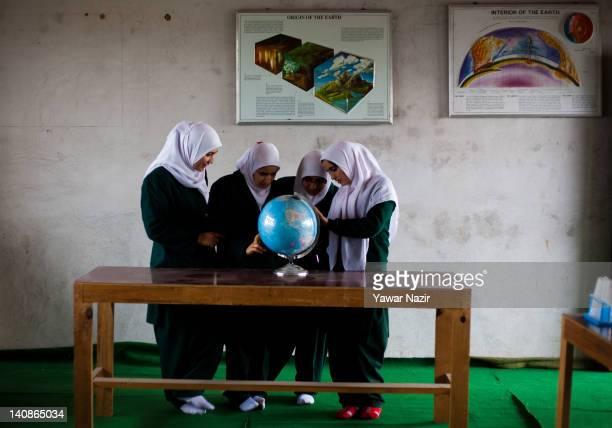 Kashmiri Muslim orphan girls looks at a globe in their school on March 7 2012 in Gopal Pora 16 Km west of Srinagar the summer capital of Indian...