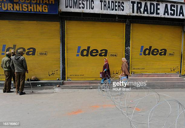 Kashmiri Muslim pedestrians walk past Indian policemen on guard during the third day of curfew imposed on the Kashmiri summer capital in Srinagar on...