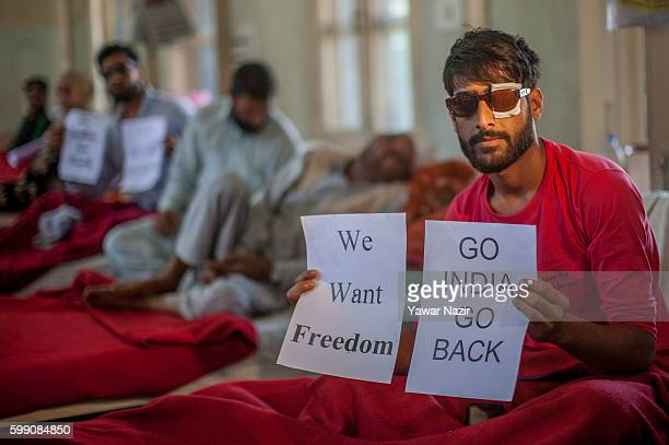 Kashmiri Muslim pellet victims who lost their vision in one or both eyes after pellets of Indian government forces hit them hold placards during a...