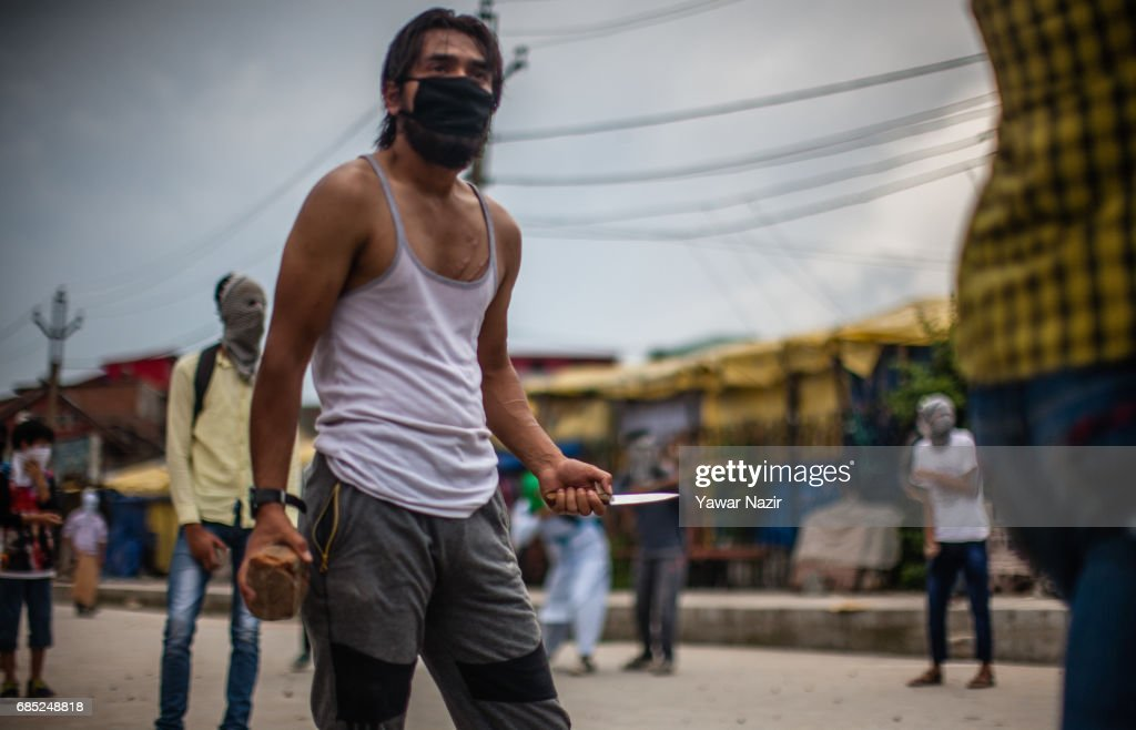 A Kashmiri Muslim protester hold bricks and a knife during an anti India protest on May 19, 2017 in Srinagar, the summer capital of Indian administered Kashmir, India. Indian government forces used teargas shells to disperse dozens of Kashmiri Muslim protesters who were throwing stones at them during an anti Indian protest in the Old City of Srinagar, after Friday prayers.
