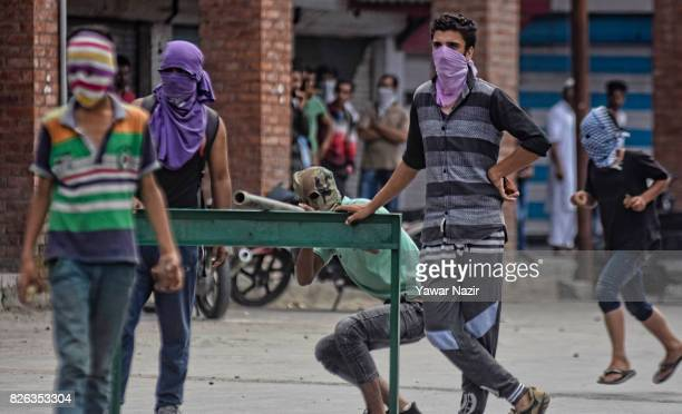 Kashmiri Muslim protester looks through a steel pipe towards Indian government forces as others hold stones before throwing them at Indian government...