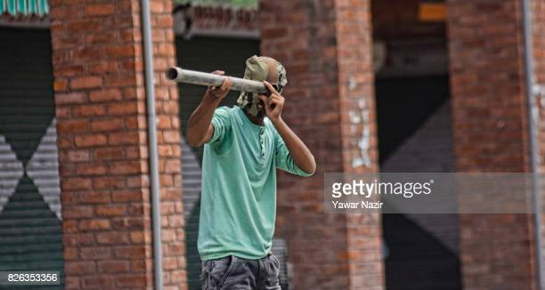 Kashmiri Muslim protester looks through a steel pipe towards Indian government forces outside Kashmir's grand mosque during an antiIndia protest on...