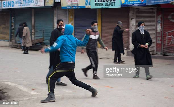 Kashmiri Muslim protester throws a stone at Indian government forces during a protest on the 24th anniversary of the 'Gaw Kadal' massacre on January...