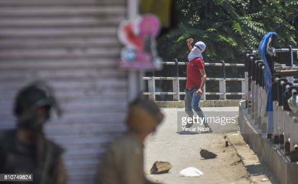 Kashmiri Muslim protester throws a stone at Indian government forces during a protest after they defied curfew on the the first death anniversary of...