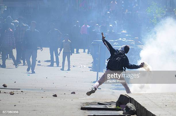 Kashmiri Muslim protester throws a tear gas canister back at Indian police in old Srinagar the summer capital of Indian controlled Kashmir Indian...