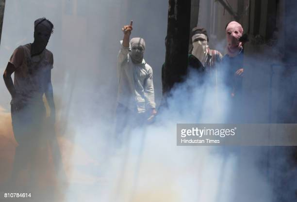Kashmiri Muslim protesters prepare to throw stones at police and paramilitary soldiers amid tear smoke during curfew in Lal Chowk area on July 8 2017...