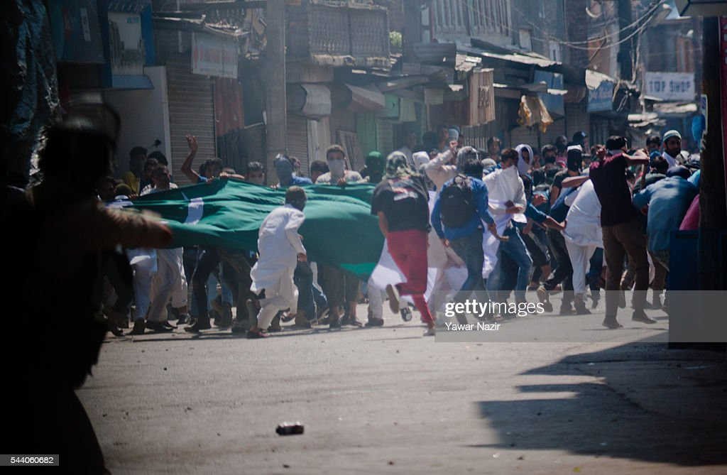 Kashmiri Muslim protesters throw stones and hold Pakistani and palestinian flags during a protest demonstration marking al-Quds (Palestine,) and Kashmir Day an annual event held on the last Friday of the Holy month of Ramadan, as a means to express solidarity with the Palestinians on July 01, 2016 in Srinagar, the summer capital of Indian administered Kashmir, India. Hundreds of thousands of Kashmiri Muslim devotees took part in the mass prayer of the last Friday, or Jummat-ul-Vida, of the holy Islamic month of Ramadan ahead of the Eid al-Fitr festival which marks the end of the fasting month of Ramadan.