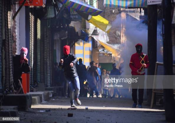 Kashmiri Muslim protesters throwing stone and bricks towards security personals amidst tear gas smoke during a protest in sopore some 55 kilometers...