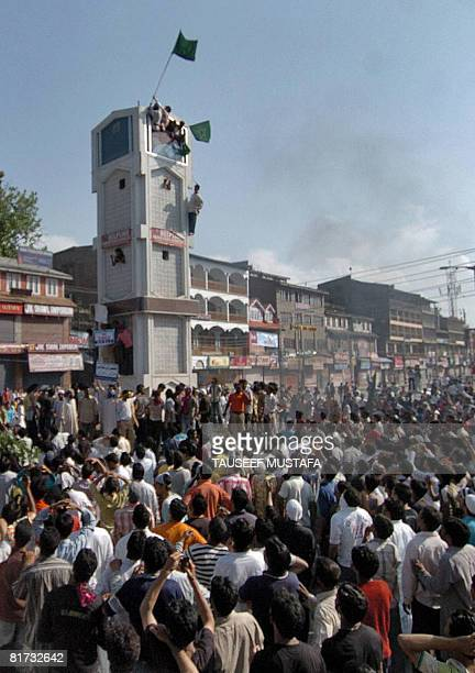 Kashmiri Muslim protestors hoist a Pakistani flag atop the clock tower in Srinagar's main commercial centre Lal Chowk during a demonstration in...