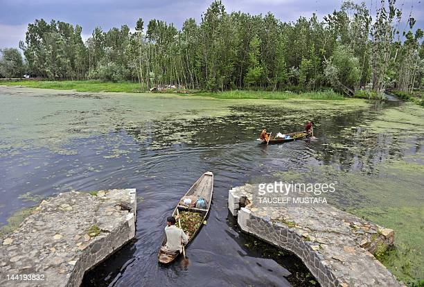 A Kashmiri muslim rides his boat in Dal Lake during a windy and rainy day in Srinagar on May 112012 Pakistan said Friday that it would host the next...