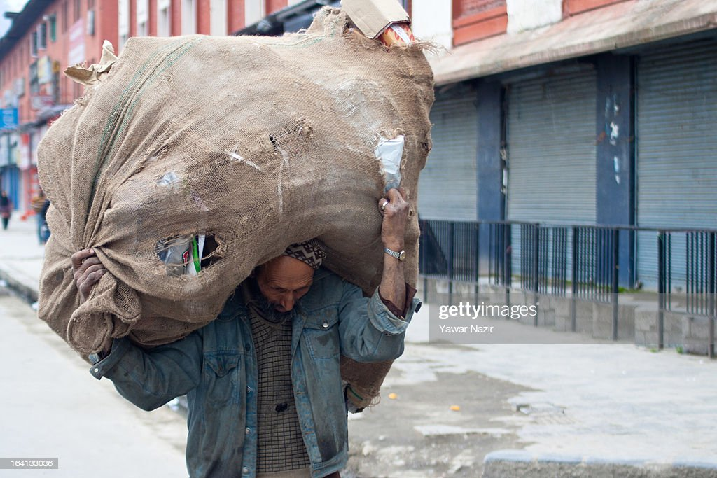 A Kashmiri Muslim scrap collector carries a heap of scraps on his head on March 20, 2013 in Srinagar the summer capital of Indian administered Kashmir, India. Kashmir has been a contested land between nuclear neighbors India and Pakistan since 1947, the year both the countries attained freedom from the British. Since 1947 the ownership of Kashmir has been disputed between Pakistan, India and China.
