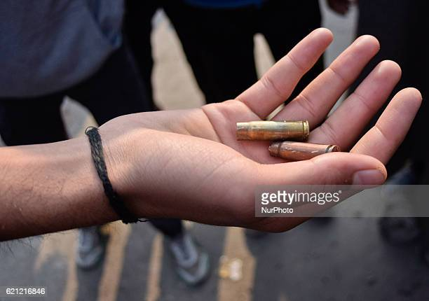 A Kashmiri Muslim show empty bullet catridges allegedly used by the Indian government forces on the mourners during the funeral of Qaisar Sofi a 16...