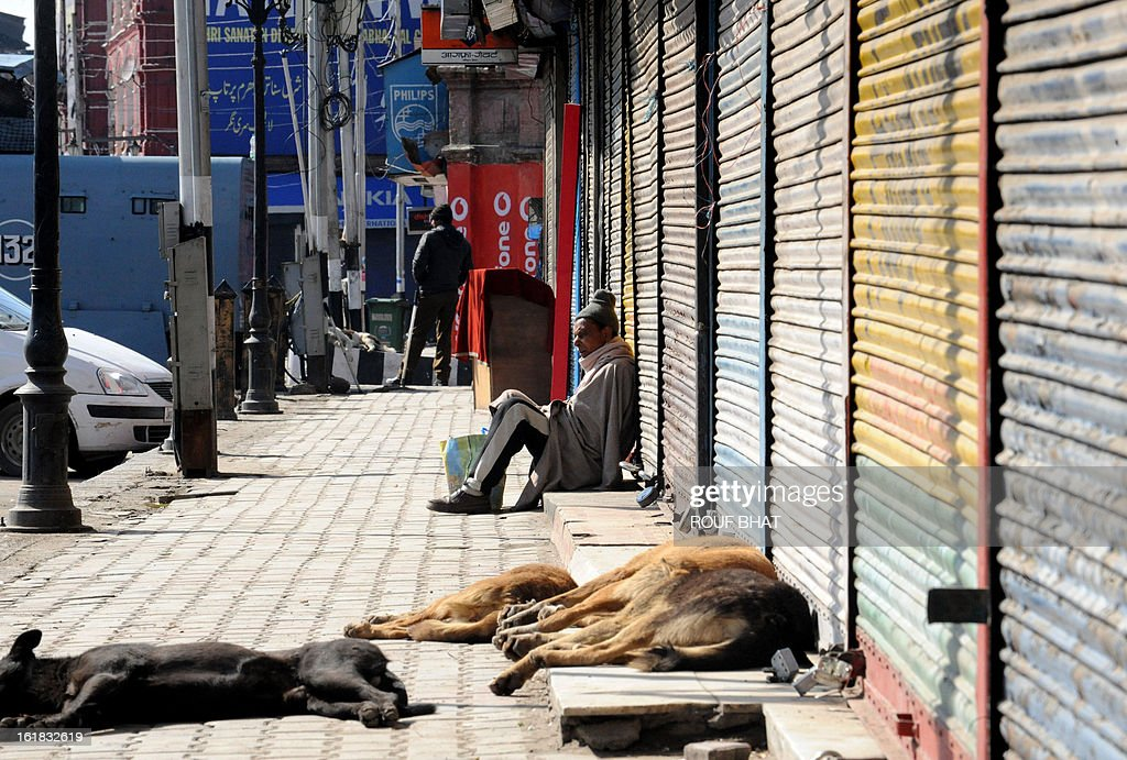 A Kashmiri Muslim sits in front of shuttered shops during the second day of strike in Srinagar on February 17, 2013. Kashmiri Hurriyat leader Syed Ali Gilani called a two-day strike in Kashmir to protest against the execution of Kashmiri Muslim separatist Mohammed Afzal Guru at a high security prison in New Delhi over his role in a deadly attack on Indian parliament in New Delhi in 2001. AFP PHOTO/ Rouf BHAT