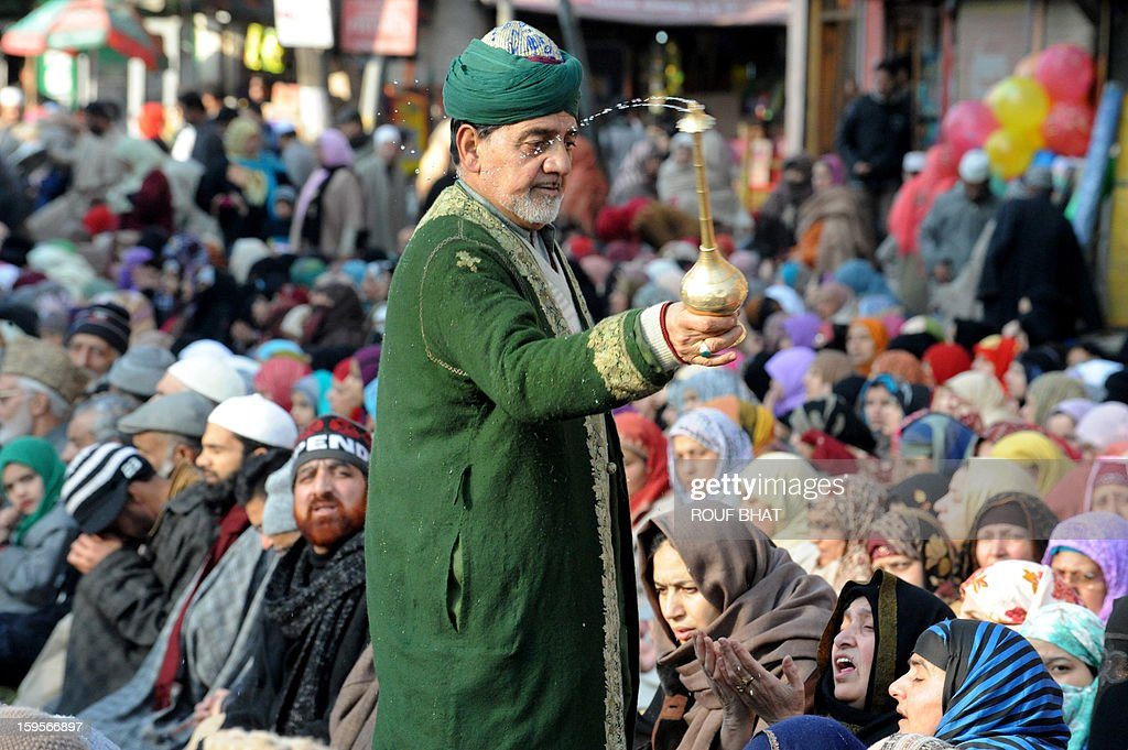 A Kashmiri Muslim sprays holy water as Kashmiri Muslims offer prayers at the shrine of Sufi saint Naqashband Sahib during an annual festival in downtown Srinagar on January 16, 2013. Thousands of people gathered to offer prayers marking the birth anniversary of Sufi saint Naqashband Sahib at his shrine in Srinagar. AFP PHOTO/ Rouf BHAT