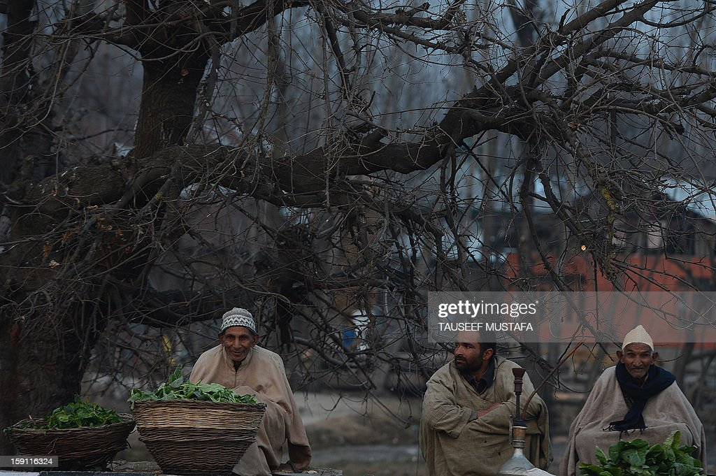 Kashmiri Muslim vegetable vendors wait for customers on a cold, winter's day in Srinagar on January 8, 2013. Kashmir Valley continued to reel under intense cold with temperatures plummeting further as Srinagar recorded the season's lowest of minus 5.5 degrees celsius. AFP PHOTO/Tauseef MUSTAFA