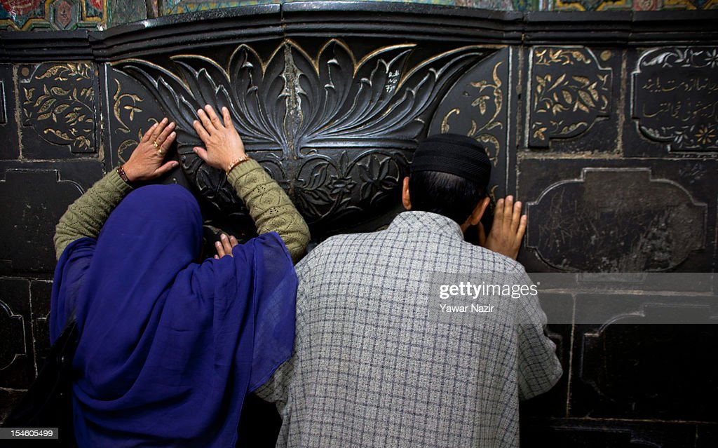 A kashmiri Muslim woman and man pray by touching the wall at the shrine of Khaniqahi mullah during a festival on October 23, 2012 in Srinagar, the summer capital of Indian administered Kashmir, India. Thousands of Muslims thronged to the shrine of Mir Syed Ali Hamadan to commemorate the anniversary of the death of the Sufi saint, Hamadan. He is believed to be responsible for the spread of Islam in Kashmir. The shrine gains a special significance on 6th of Zilhaj (last month of Muslim calendar), the death anniversary of Mir Syed Ali Hamadan. On this day, devotees visit the shrine in large numbers to pay a tribute to saint Hamadan.