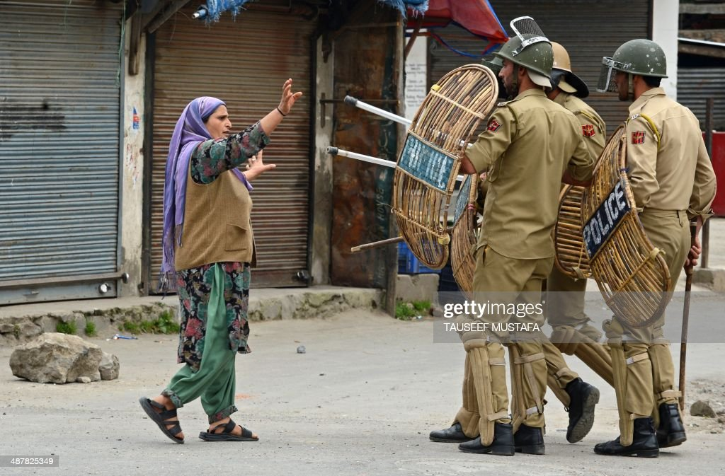 A Kashmiri Muslim woman comfronts Indian policemen after they arrested a youth during a protest at Hyderpora locality in Srinagar on May 2, 2014. Parts of Kashmir remained under curfew for the second day following tension over the killing a youth by government forces firing on poll day two days earlier.Kashmir is divided between India and Pakistan, with both claiming the disputed Muslim-majority territory in full since 1947 when the two countries gained independence from Britain.The insurgency has left tens of thousands, mostly civilians dead since 1989. AFP PHOTO / Tauseef MUSTAFA