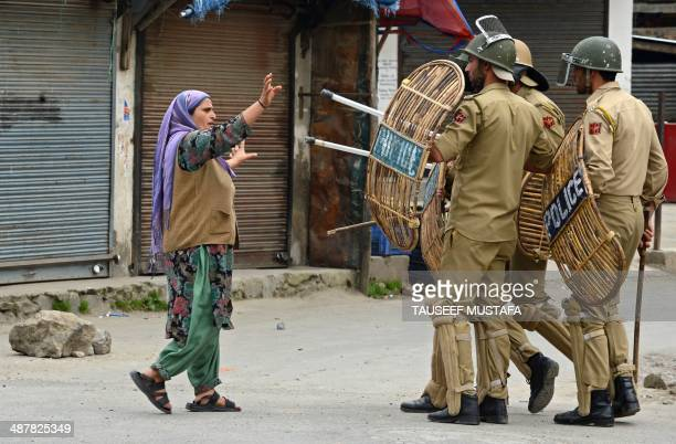 A Kashmiri Muslim woman comfronts Indian policemen after they arrested a youth during a protest at Hyderpora locality in Srinagar on May 2 2014 Parts...