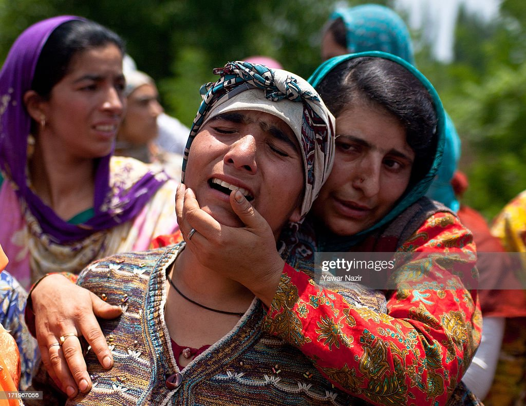 A Kashmiri Muslim woman consoles a relative of Tariq Ahmad, a civilian who was killed by Indian army during his funeral on June 30, 2013 in Kondebal 25 km (15 miles) north of Srinagar the summer capital of Indian administered Kashmir, India. A teenage boy, identified as Irfan Ahmad Ganaie was killed during a search operation by Indian police in the village of Markondal in Bandipora District, before dawn on Sunday. A second person, Tariq Ahmad Leharwal, was killed after the Indian army shot at local residents who were protesting the earlier deadly incident. The killings triggered mass protests in the area.