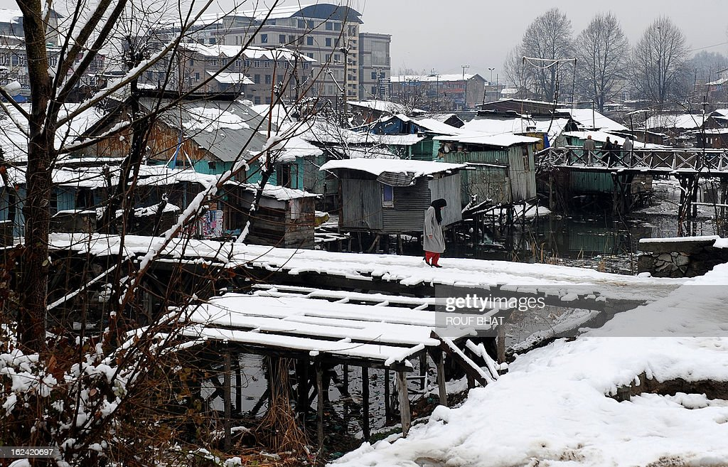 A Kashmiri Muslim woman crosses a foot-bridge after a snowfall in Srinagar on February 23, 2013. The Jammu-Srinagar National Highway remained closed for the second day as fresh snowfall across Kashmir prompted authorities to issue an avalanche warning in higher reaches of the Valley. AFP PHOTO/ Rouf BHAT