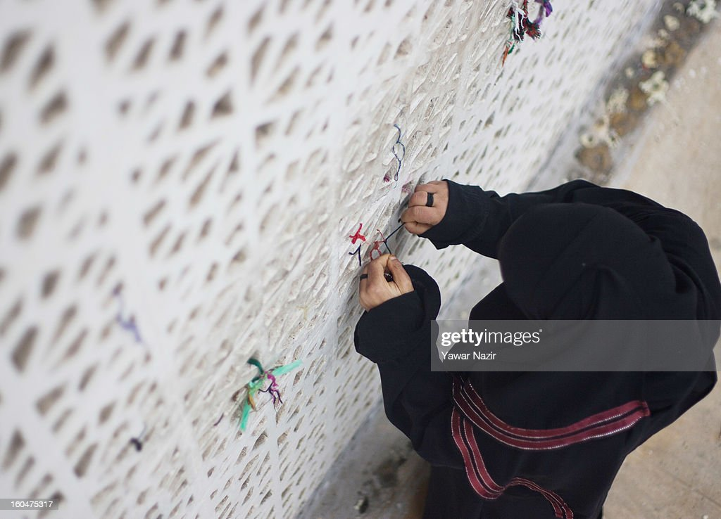 A Kashmiri Muslim woman devotee ties a 'Desh', or a votive thread, to the fence at Hazratbal shrine on the Friday following Eid-e-Milad , or the birth anniversary of Prophet Mohammad on February 01, 2013 in Srinagar, the summer capital of Indian administered Kashmir, India. Thousands of Muslims from all over Kashmir visit the Hazratbal shrine in Srinagar to pay obeisance on the Friday following Eid-e-Milad , or the birth anniversary of Prophet Mohammed. The shrine is highly revered by Kashmiri Muslims as it is believed to house a holy relic of the Prophet Mohammed. The relic is displayed to the devotees on important Islamic days such as the Eid- Milad when Muslims worldwide celebrate.