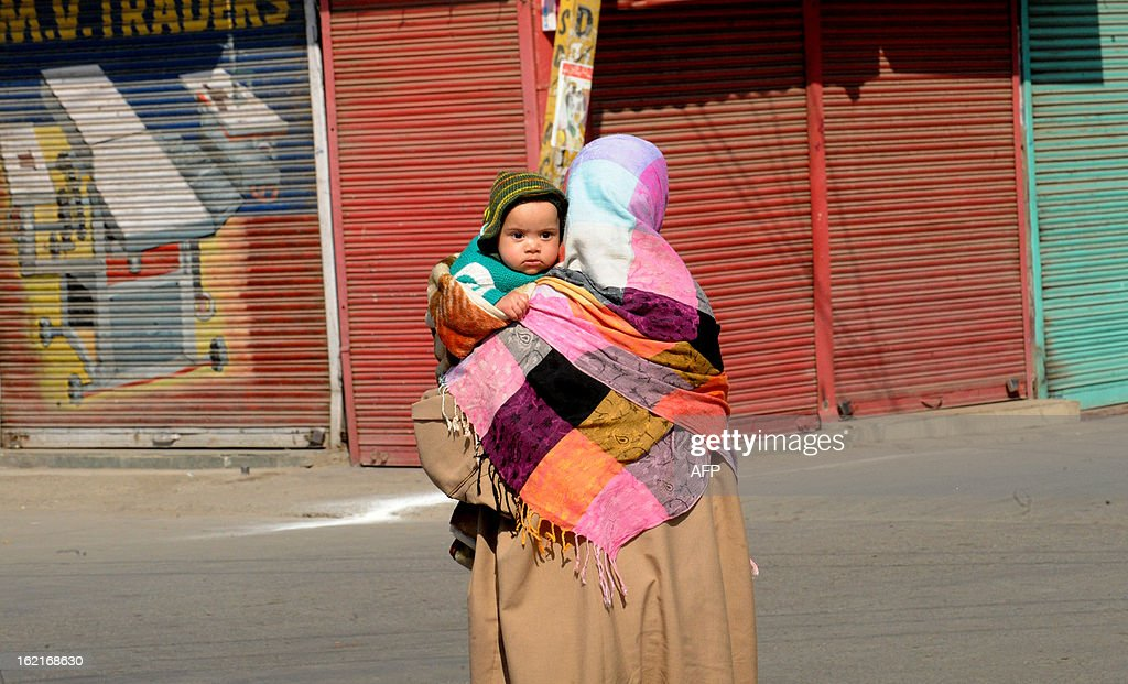A Kashmiri Muslim woman holds her child as she walks during a shutdown in Srinagar on February 20, 2013. A separatist alliance, All Parties Hurriayt Conference, opposed to Indian rule in Kashmir called for a two-day strike in to press the demanded for return of Afzal Guru's mortal remains to his family. Guru was executed on February 9, 2013 and buried inside a high security prison in New Delhi after he was convicted of his role in a deadly attack on Indian parliament in 2001. AFP PHOTO/ Rouf BHAT