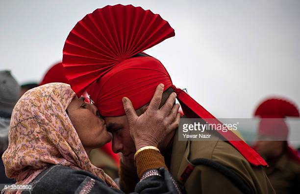 Kashmiri Muslim woman kisses her son after his passing out parade parade at a garrison in Rangreth on March 05 2016 in the outskirts of Srinagar the...