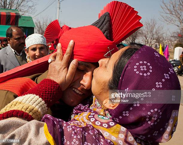Kashmiri Muslim woman kisses her son who passed after his passing out parade at Rangreth in a garrison on March 8 2014 in the outskirts of Srinagar...