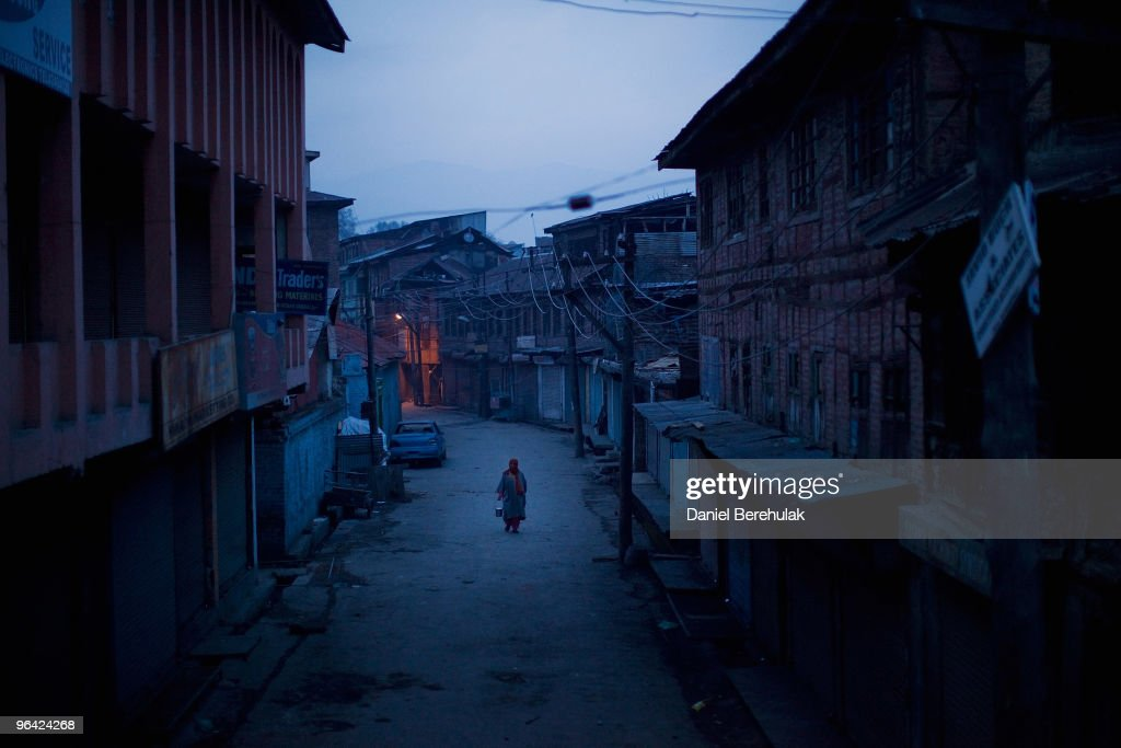 Kashmiri muslim woman negotiates curfew imposed streets on February 04 2010 in Srinagar Kashmir India Soldiers dressed in riot gear patrolled the...