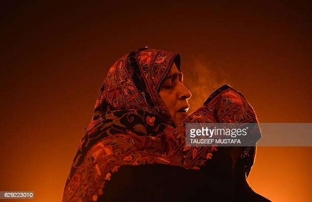 A Kashmiri Muslim woman prays as a priest displays a relic believed to be a hair from the beard of Prophet Muhammed during EideMiladunNabi the...