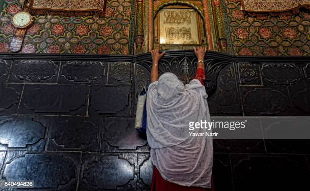 Kashmiri Muslim woman prays as she touches the wall of the shrine of Khaniqahi mullah during a festival on August 29 2017 in Srinagar the summer...