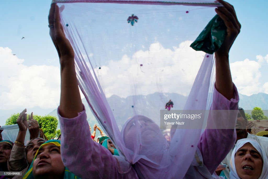A Kashmiri Muslim woman prays as they watch a head priest displays a holy relic believed to be the hair from the beard of the Prophet Mohammed during the last Friday on the occasion of the Muslim festival Mehraj-u-Alam at the Hazratbal Shrine on June 14, 2013 in Srinagar, the summer capital of Indian administered Kashmir, India. Mehraj-u-Alam marks the night Muslims believe Prophet Mohammed ascended to the heaven. Every year thousands of devotees from across Kashmir throng the Hazratbal shrine for prayers and glimpse the Moi-e-Muqaddas, a Holy Relic of Prophet Mohammed, that is displayed for public viewing on ten occasions in a year.